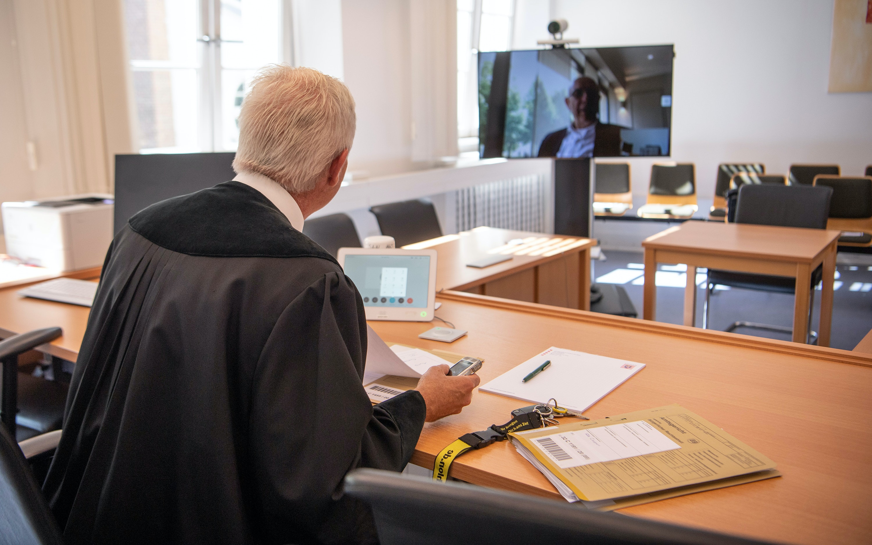 A German court talks to a lawyer through a camera during COVID-19.