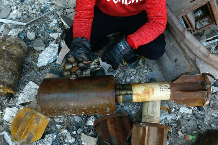 A person next to debris and bomb parts