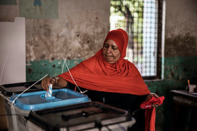 A woman casts her ballot at a polling station in Stone Town, Zanzibar