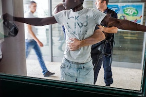 A man pressed up against a window with arms spread
