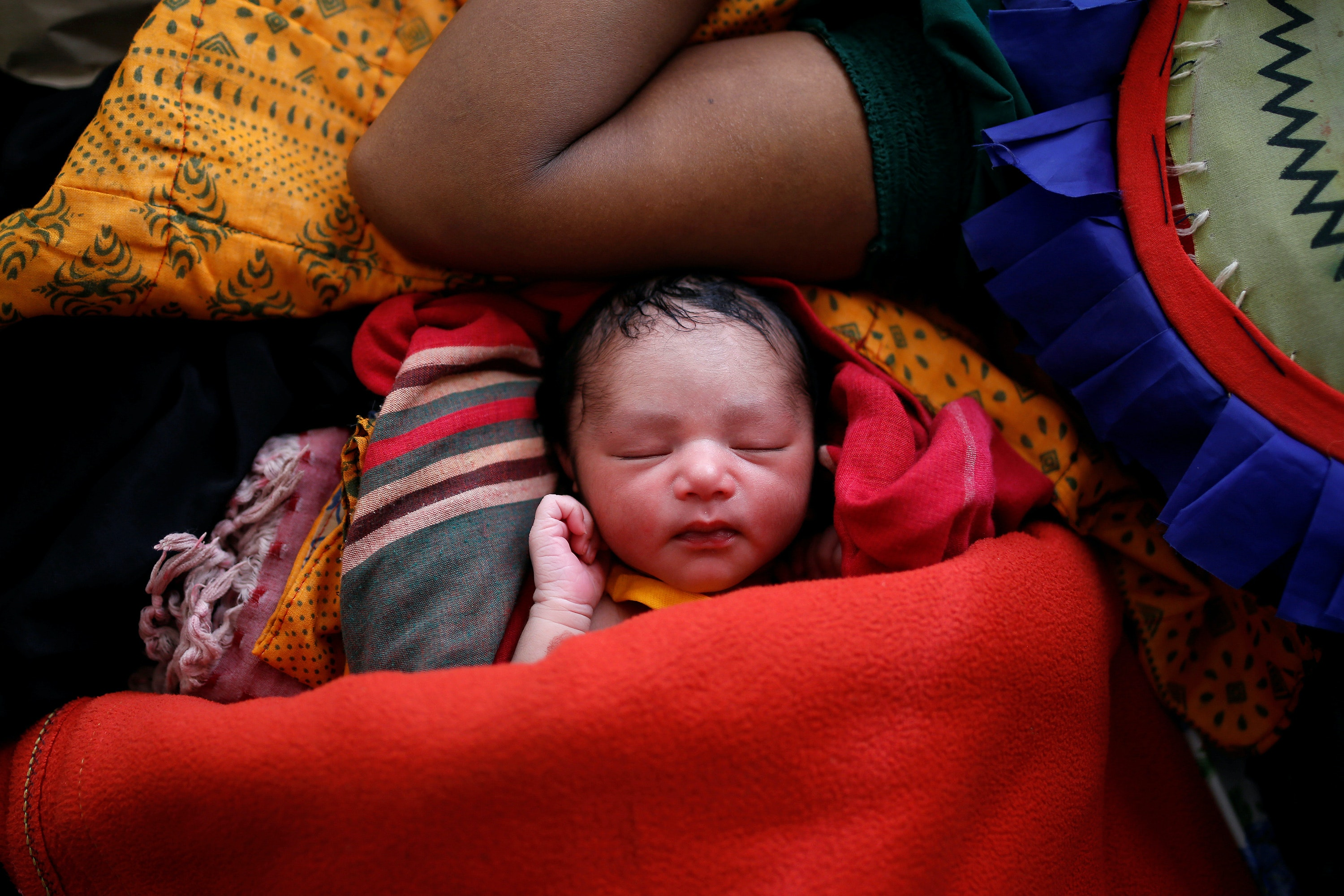 A newborn baby wrapped in a red blanket