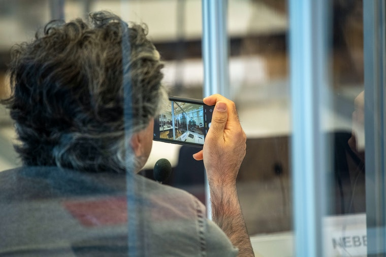 A man photographed through plexiglass panels taking a photo with a mobile phone