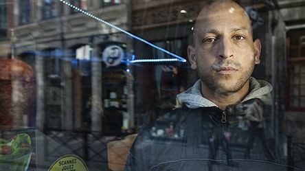 A man behind a glass storefront