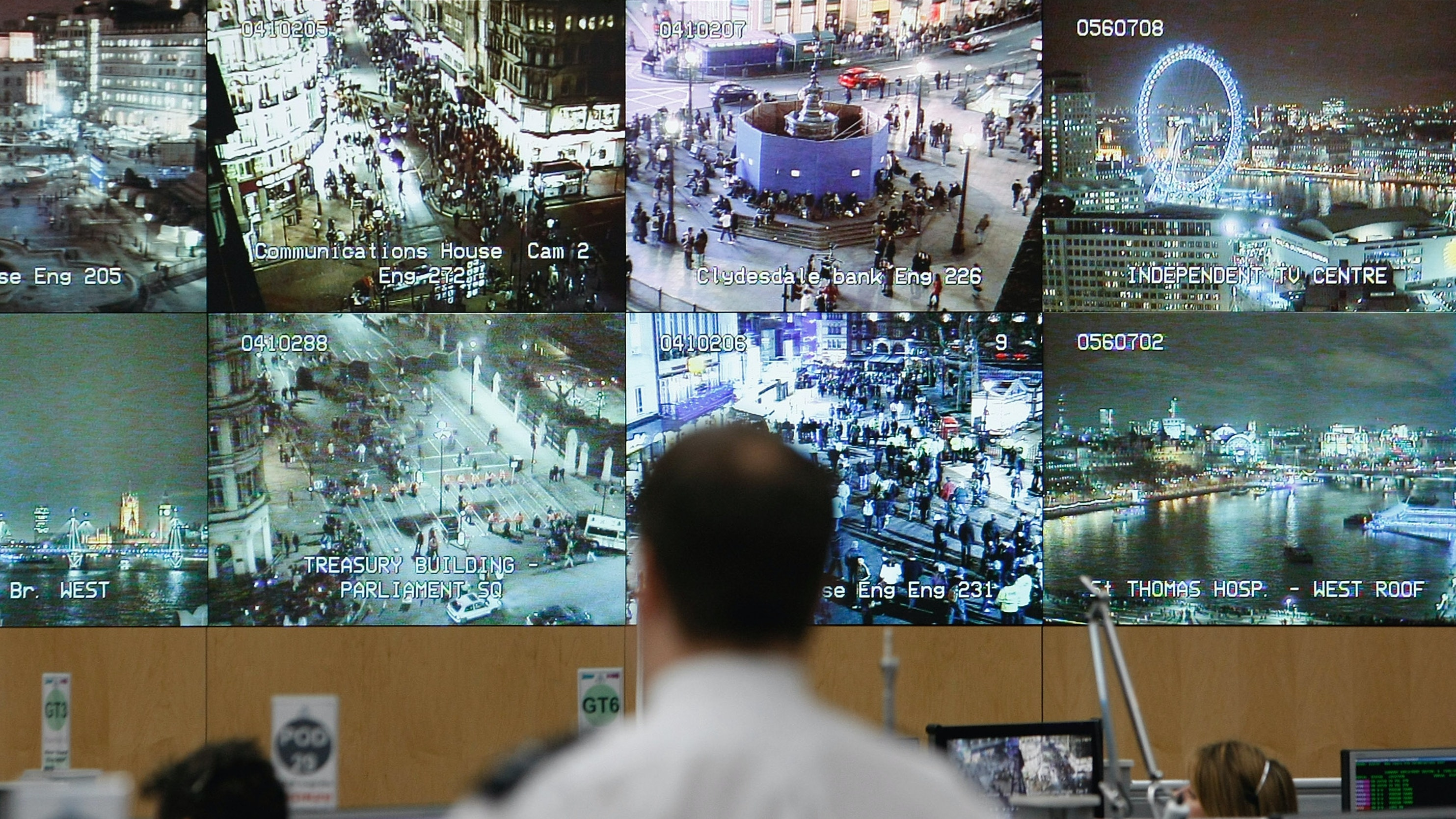 A bank of video monitors diplay footage at a police operations office.