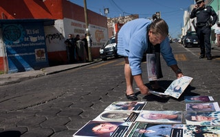A woman placing photographs on a street