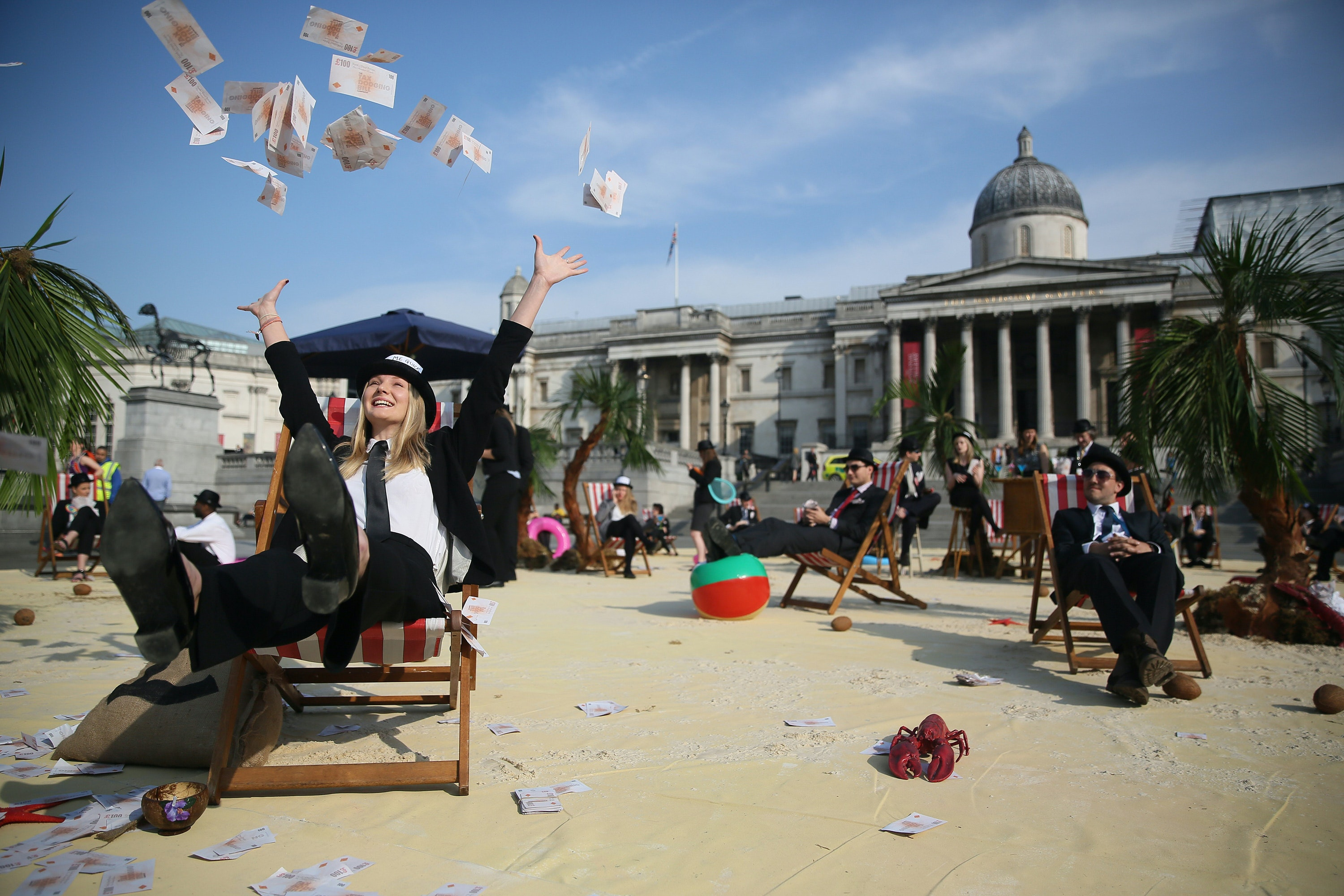 Demonstrators in fancy costume tossing play money in the air