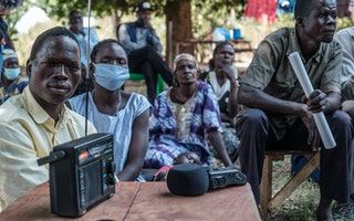 A community listens to the ICC verdict broadcasted in Lukodi, Uganda