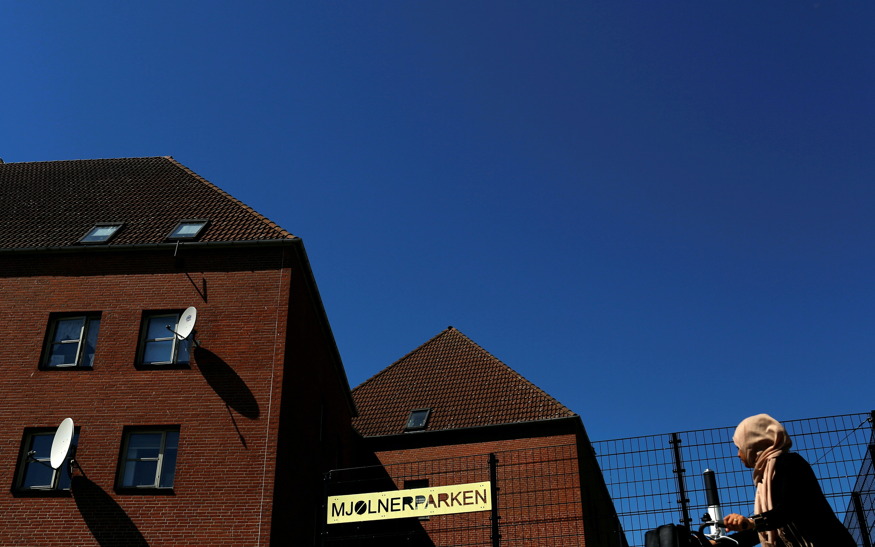 A woman in a pink headscarf walks past red brick buildings under a blue sky