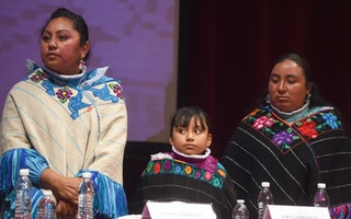 Two indigenous women and a child at a ceremony in Mexico City