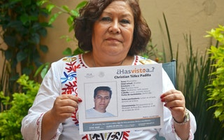 Mother holding sign of disappeared son