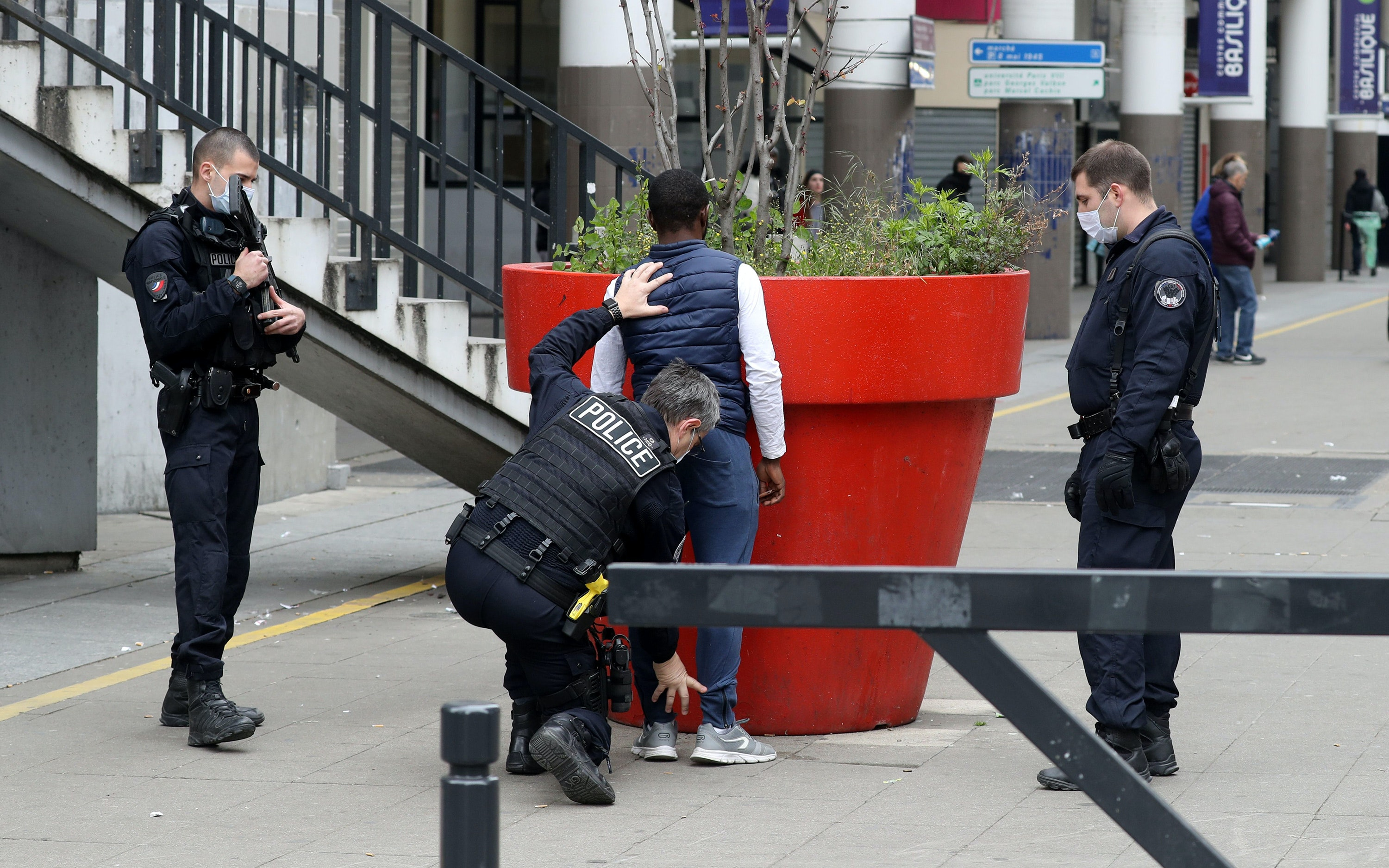 A police officer searches a man in a pedestrian plaza