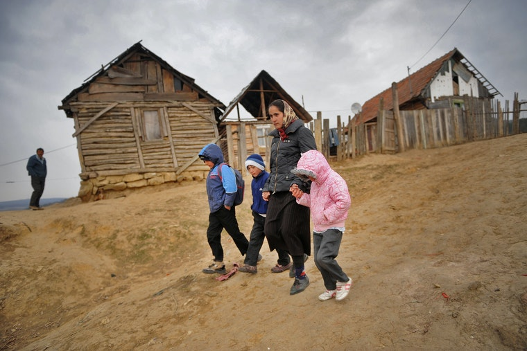 A woman and three children walking on an unpaved road
