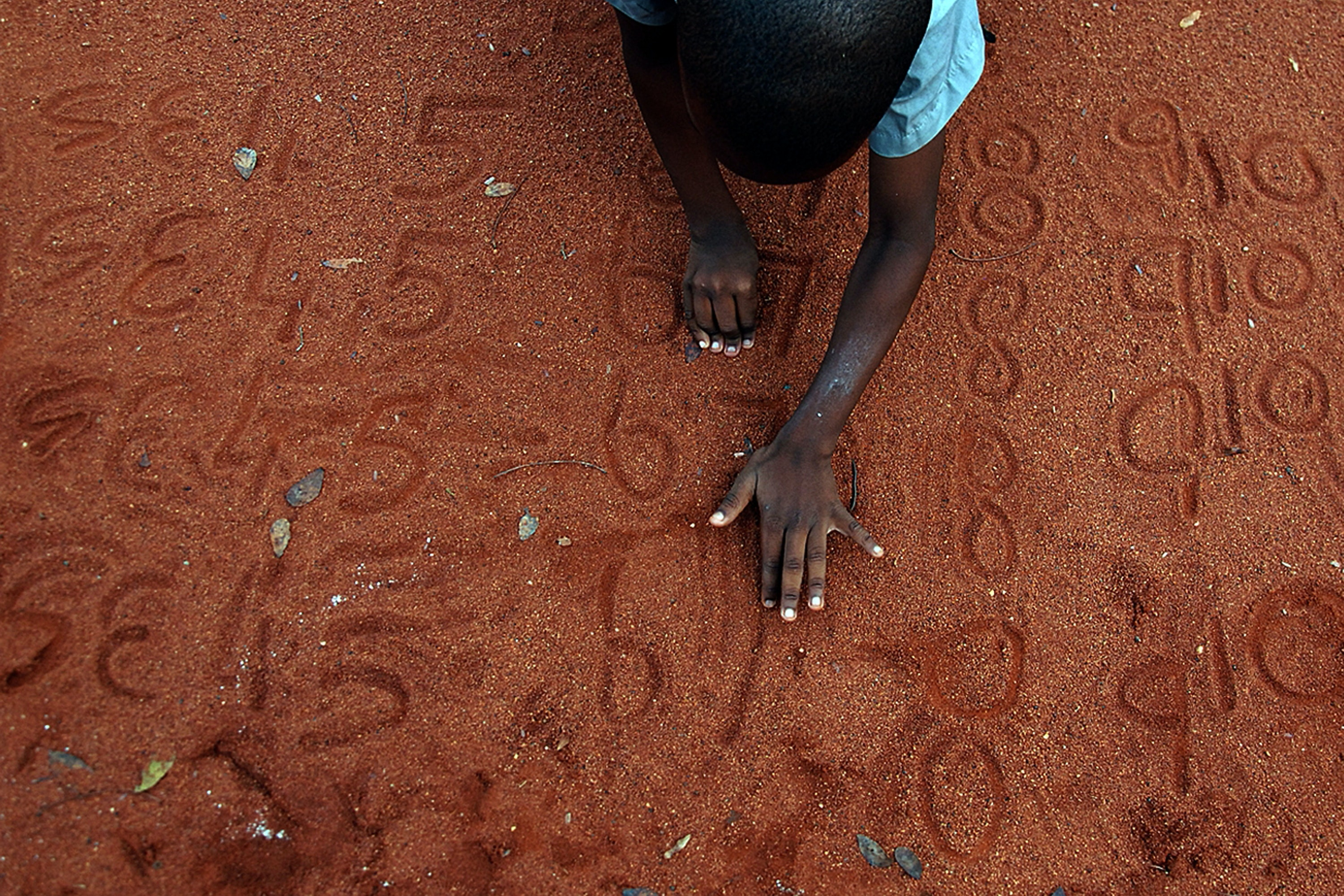 A boy writing numbers in the sand
