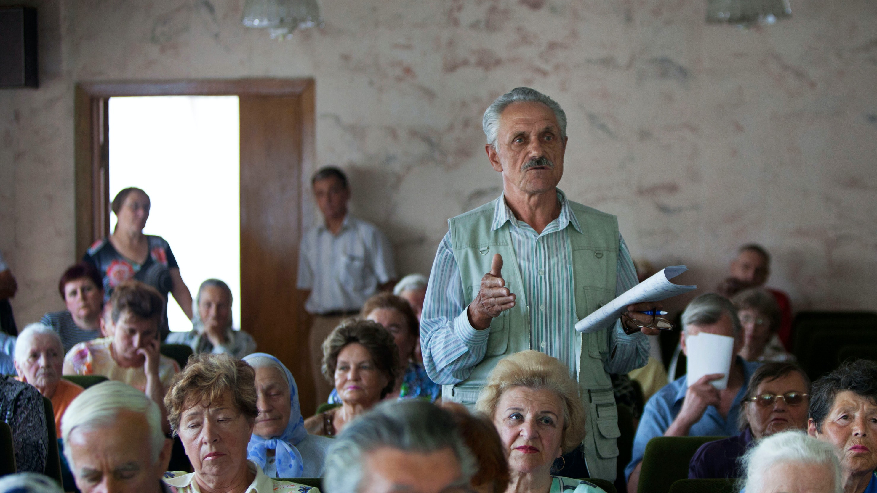 An elderly man stands above a crowd in Ukraine