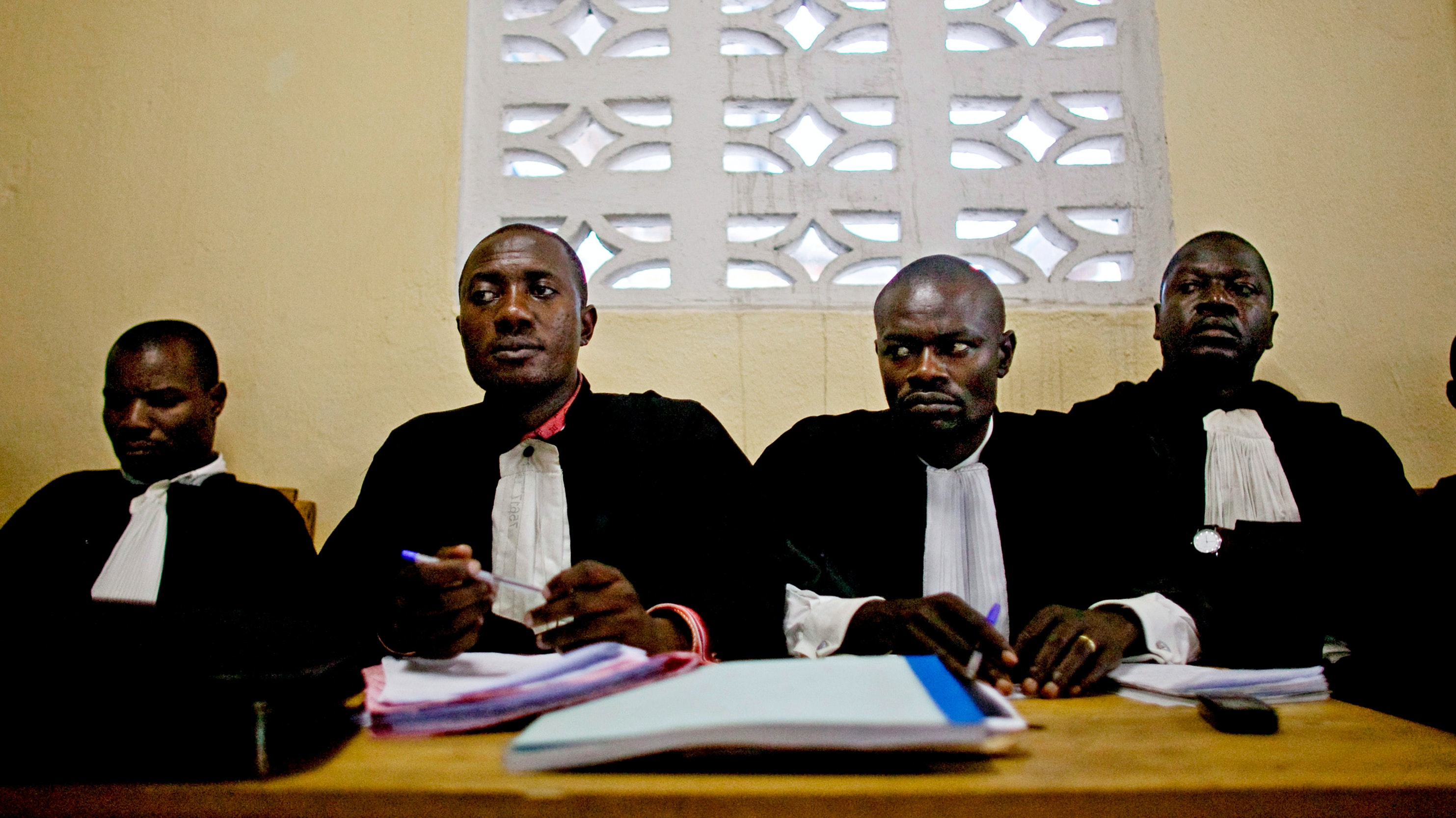 A group of men in legal robes listens to testimony.