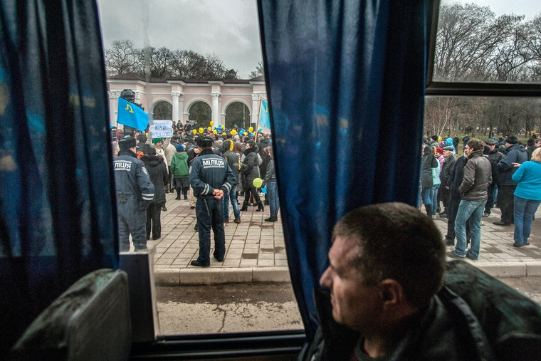 A man views a crowd of protesters from inside a bus