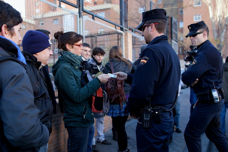 A woman in a group handing her identification card to a police officer