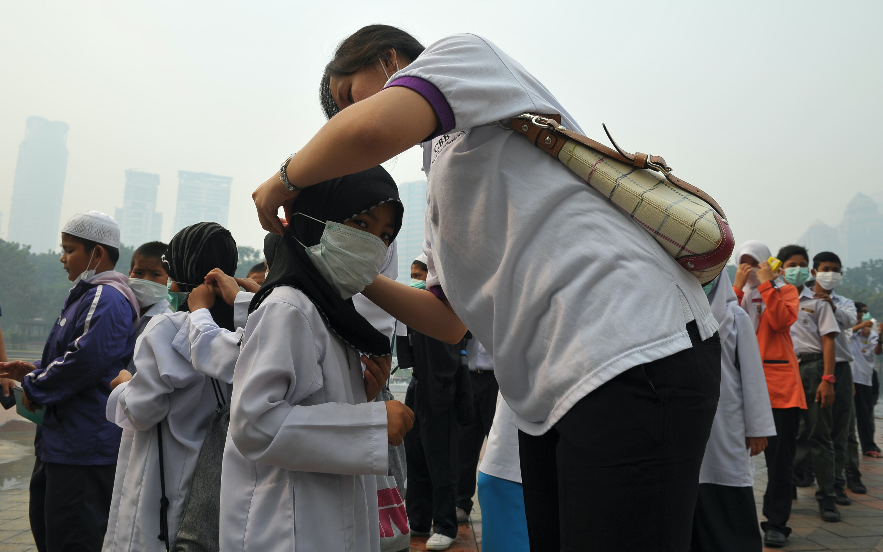 A group of students and a teacher under a haze filled sky
