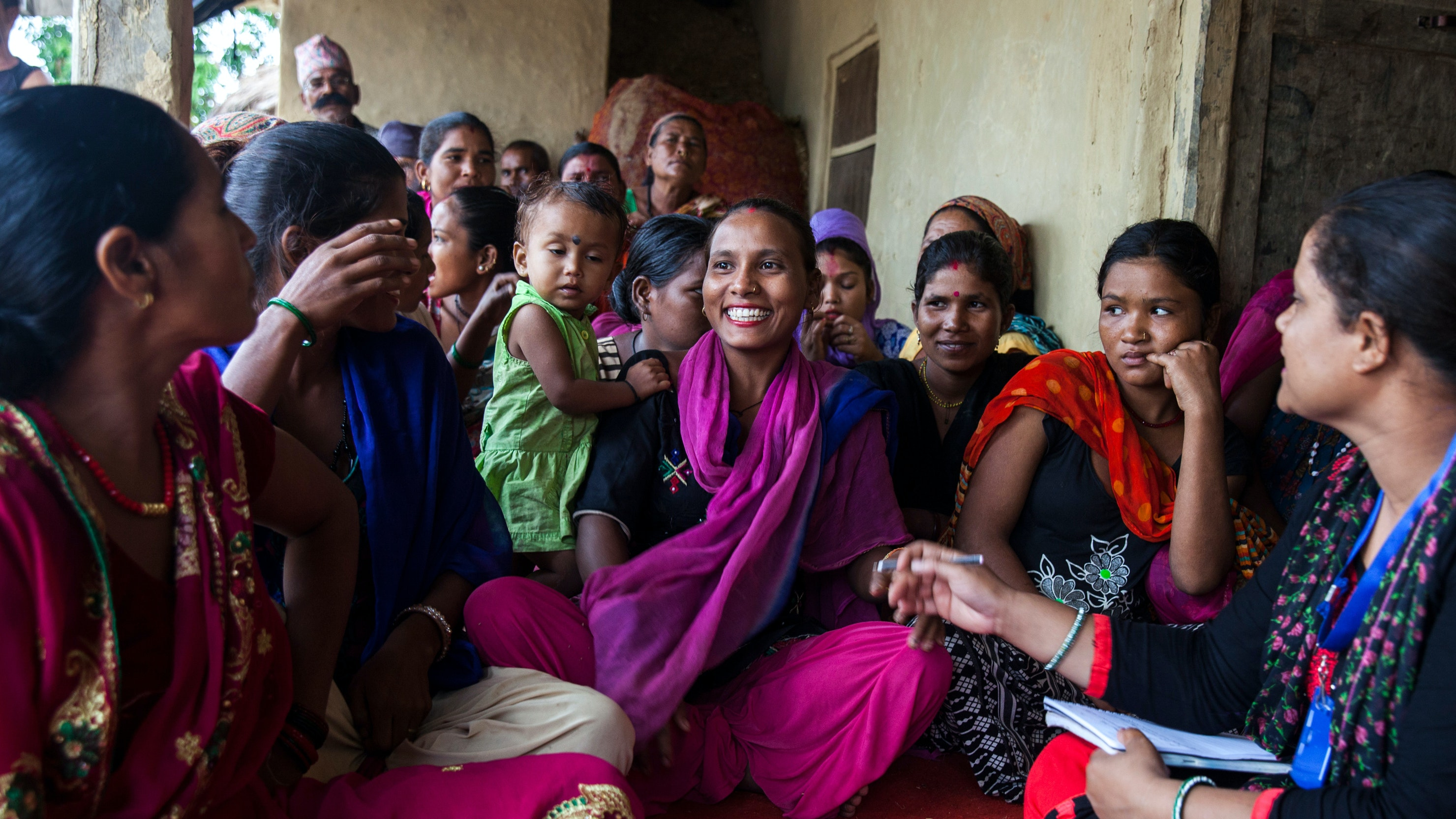 A  woman sitting down and holding a notepad speaks with members of a village in Nepal.