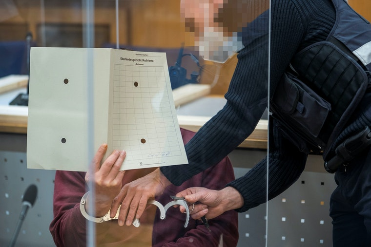 A man in handcuffs hides his face in a courtroom