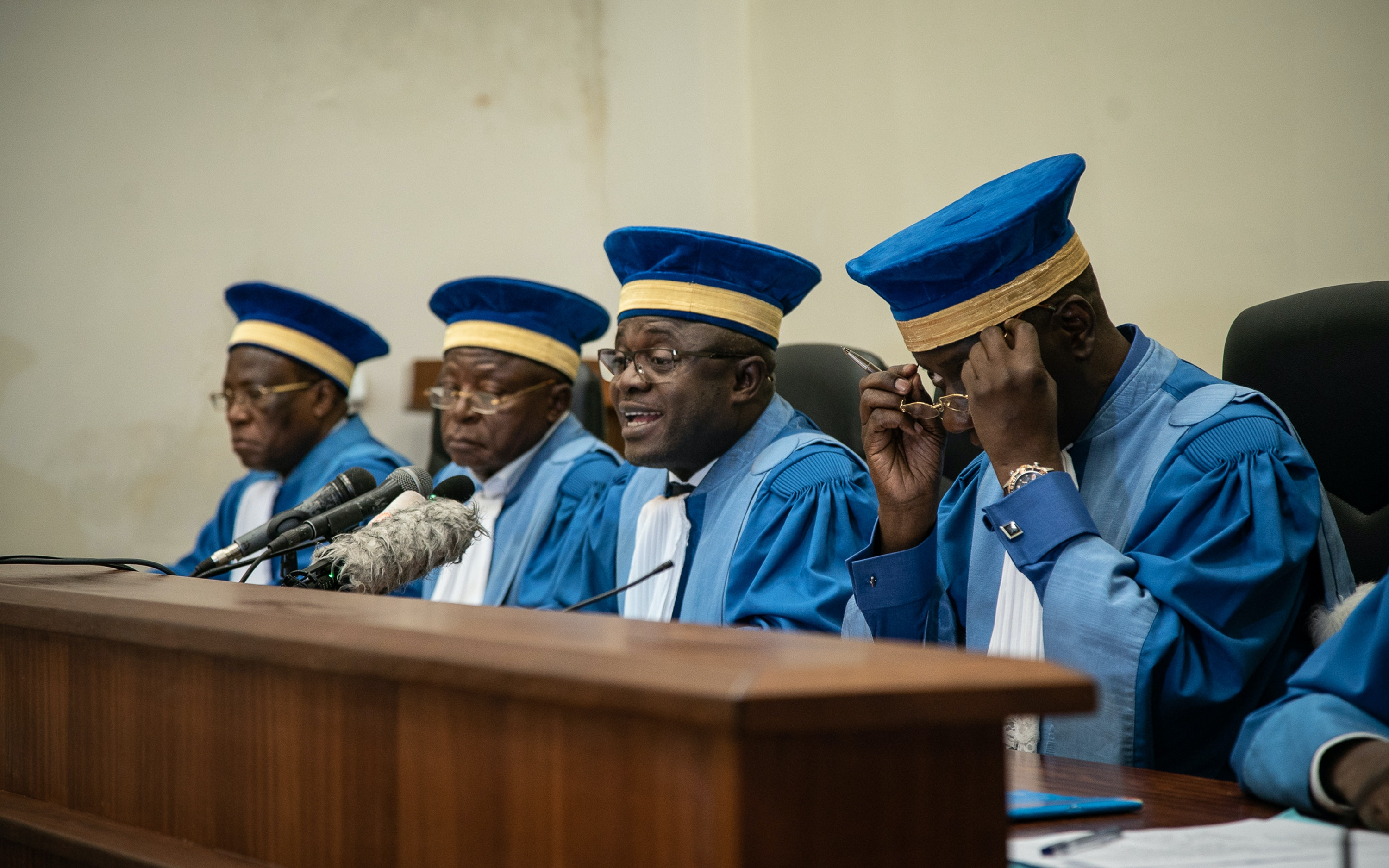 Judges wearing blue caps and robes sit atop a bench in a courtroom