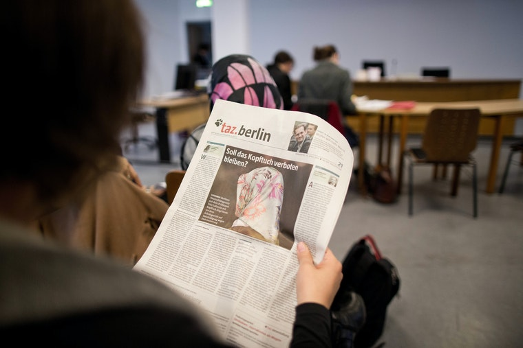 A woman reading a German newspaper