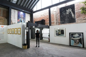 A person standing in an open gallery space